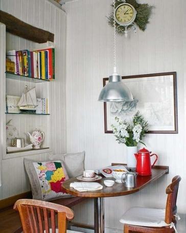 Esté desayunador se dispuso alrededor de una mesa empotrada en la pared, un simple banco con almohadones que aportan color y un par de sillas Windsor completan el equipamiento. Se aprovecho un nicho en la pared para crear una minibiblioteca.