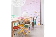 Un comedor descontracturado y femenino. Las sillas de distintos colores aportan frescura, mientras que el fondo rosa enmarca el espacio.