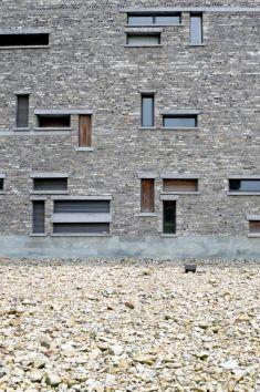 A partir de millones de tejas y ladrillos reciclados, un equipo de 50 artesanos preparó el conglomerado gris con salpicaduras naranjas que reviste las fachadas