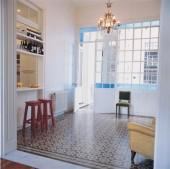 Bajo los paños vidriados superiores y el marco existente se armó una barra-desayunador con estantes, muy útiles para guardado.